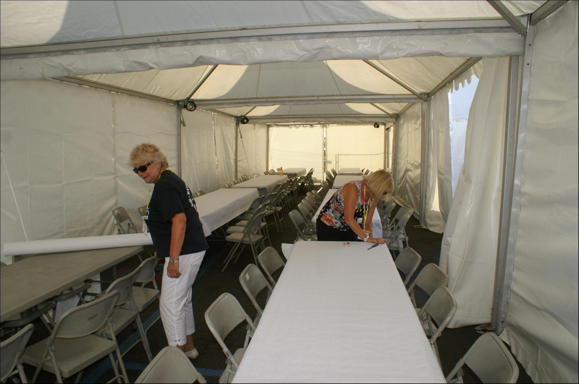 Sous les tentes on prépare les tables.jpg